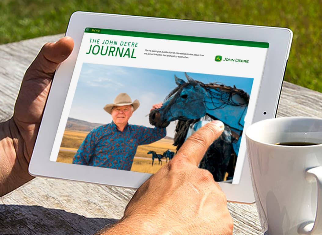 A pair of hands hold and iPad that displays an article from the John Deere Journal