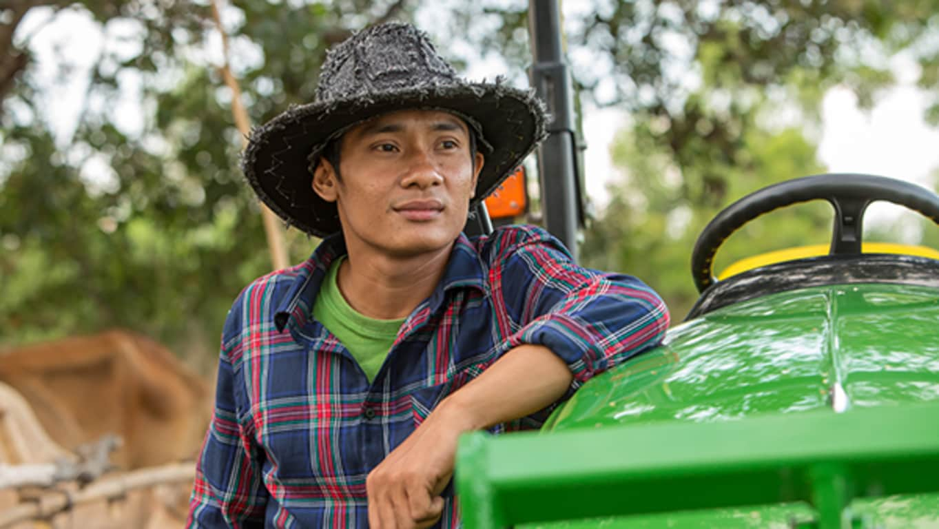 A man wearing a hat stands along side his John Deere utility tractor
