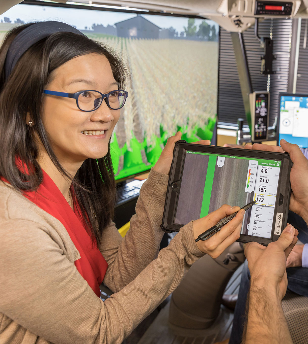 Woman points with stylus, showing information to a man. Tractor simulator in the background.