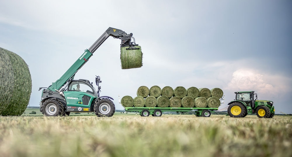 John Deere and Kramer agriculture equipment moving hay bales