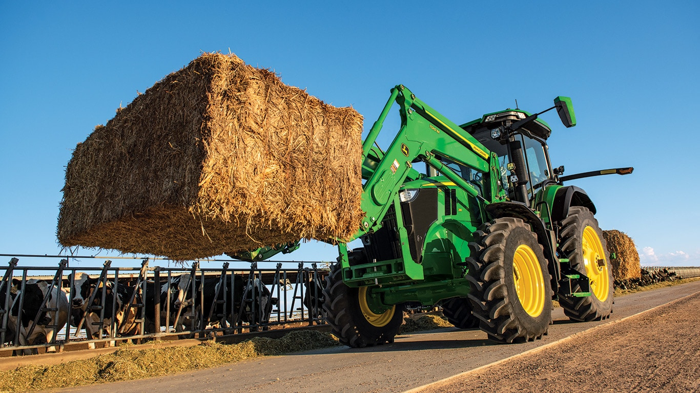 New 7R 210 with loader and a bale of hay