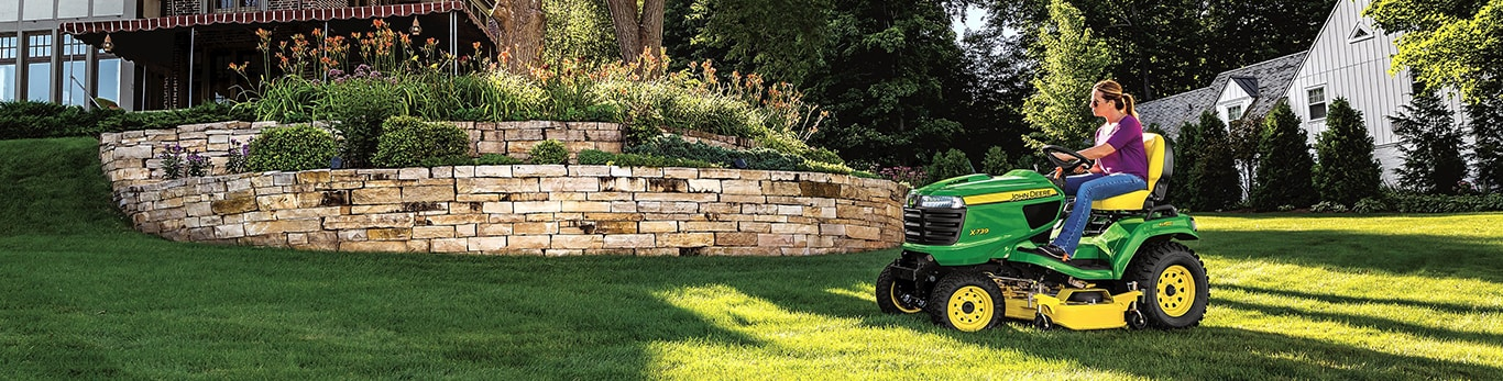 woman mows lawn on a John Deere riding mower