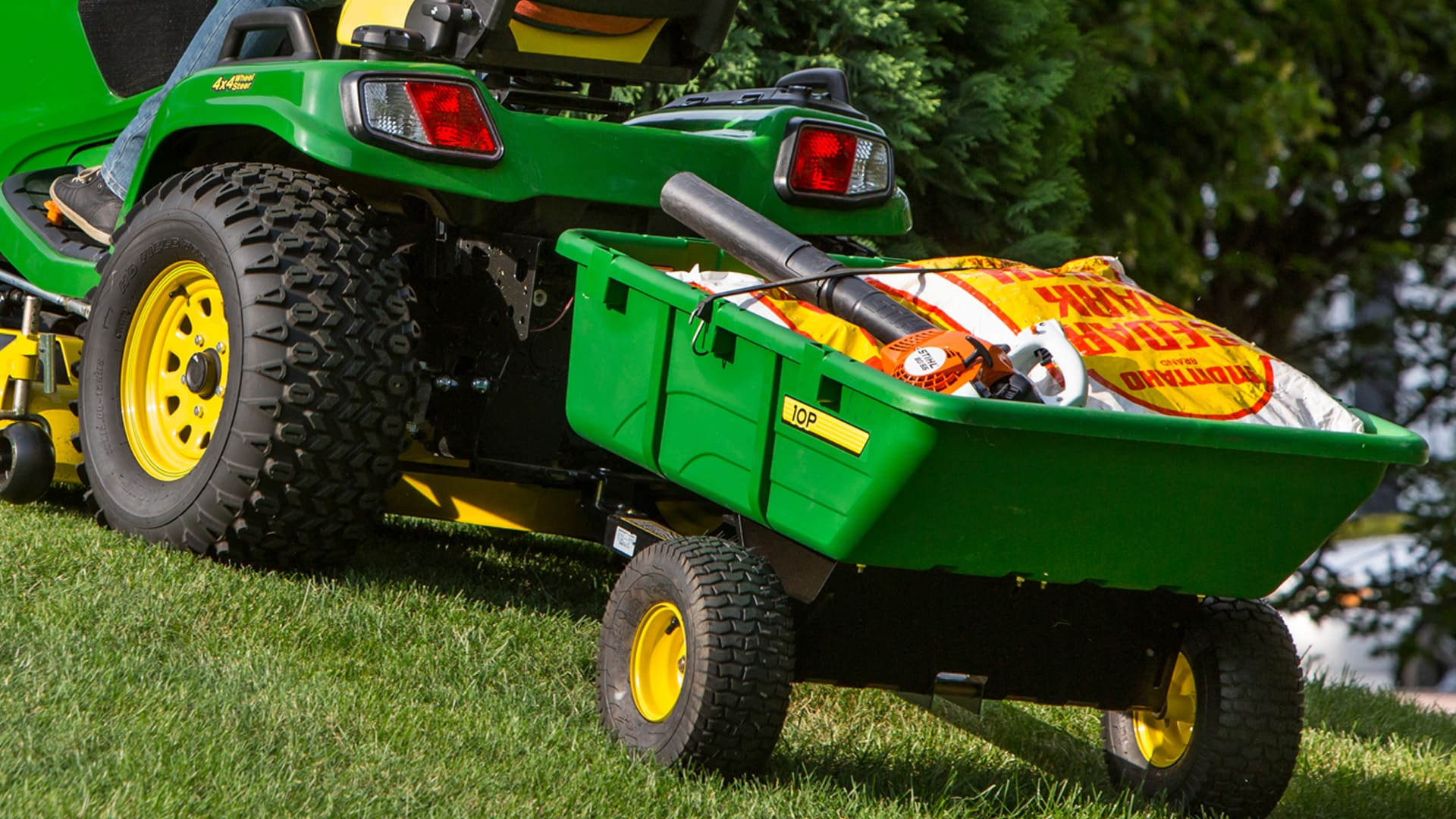 Closeup shot of a ride-on mower pulling a cart