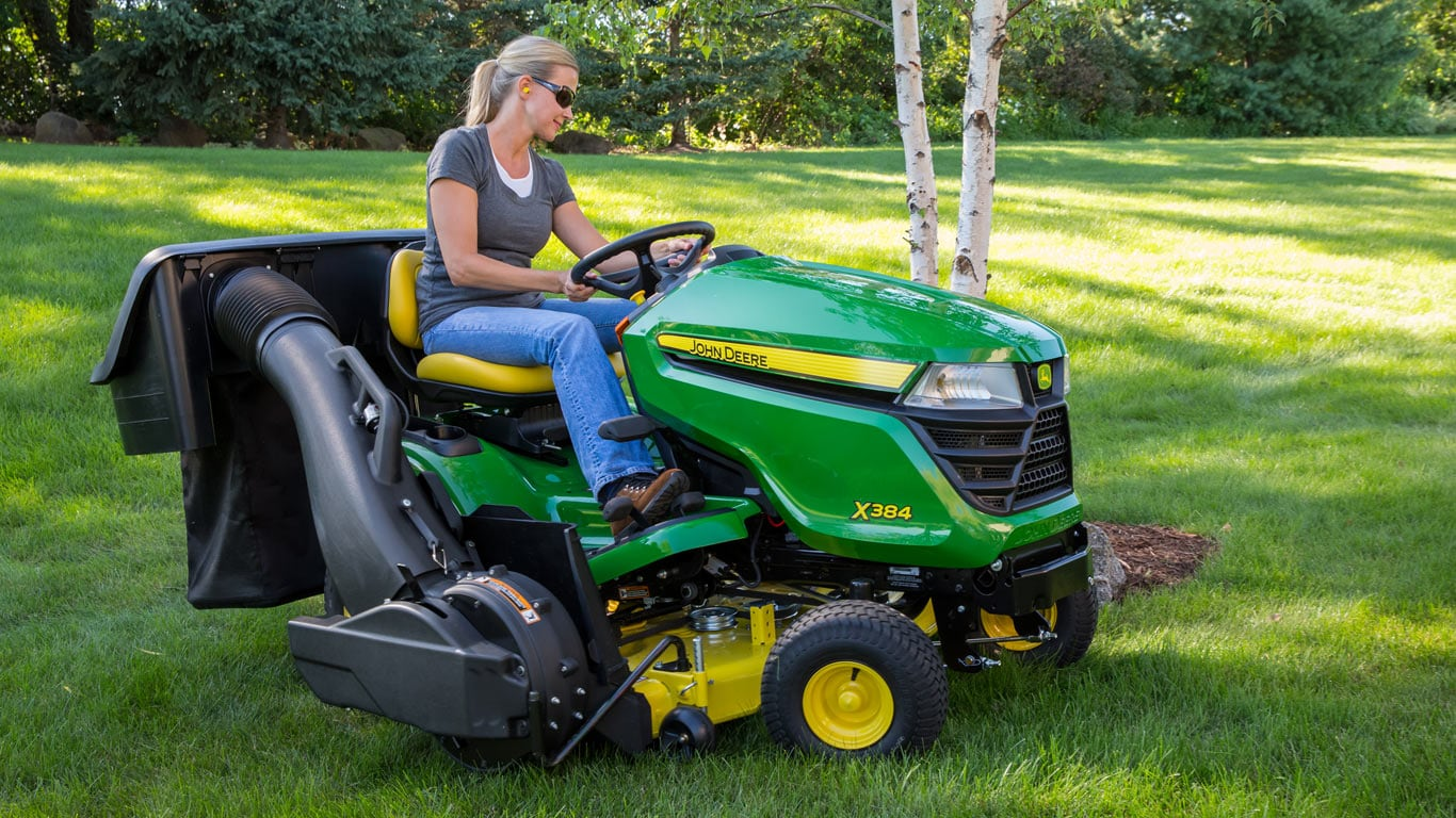 image of woman on lawn tractor with collection system attached